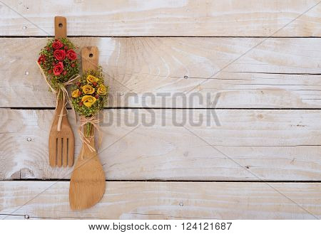 Wooden background with kitchen utencils decorated with flowers
