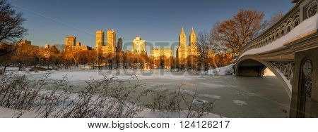 Panoramic winter sunrise on frozen Central Park Lake with Bow Bridge and view of Upper West Side buildings. Manhattan, New York City