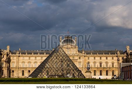 Paris, France May 26 2015 - The Louvre in late afternoon light with storm clouds behind
