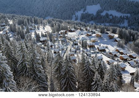 Elevated view looking down on the snow covered rooftops of an idyllic alpine village in Barboleuse, Switzerland.