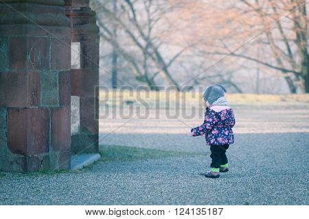 Little baby toddler curiously exploring outdoors world in winter