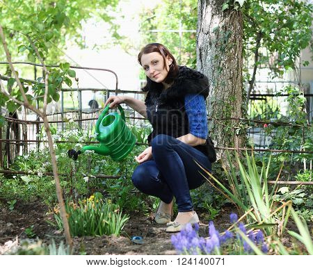 Positive casual dressed woman in yard gardening waters flowers