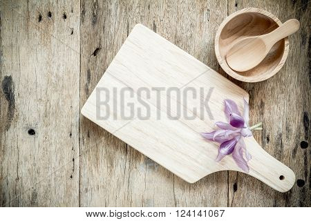 Wooden chopping board on old wooden table. Top view.
