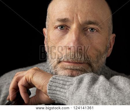 confident and positive 60 years old man with a beard - a headshot against a black background