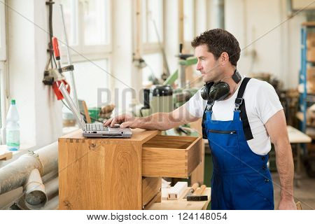 worker in a carpenter's workshop using computer