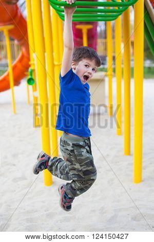 Little boy climbing on jungle gym, outdoor