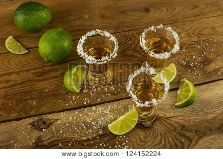 Tequila shots with lime and salt on the wooden background top view. Tequila. Gold Mexican tequila. Tequila shot