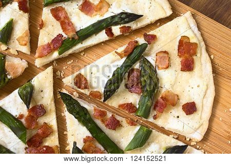 Green asparagus and bacon tarte flambee or Flammkuchen a typical Alsatian and South German dish photographed overhead on wooden board with natural light poster