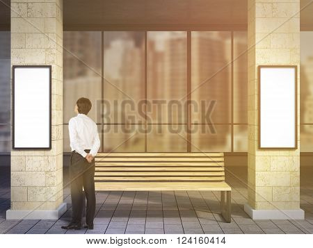 Businessman near bench under portico between columns looking at blank poster. Toned filter. Concept of waiting at bus stop.