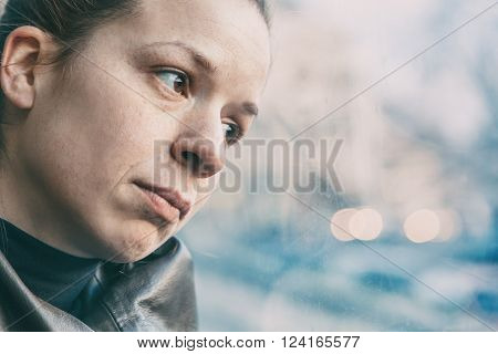 Woman sitting in streetcar alone and annoyed