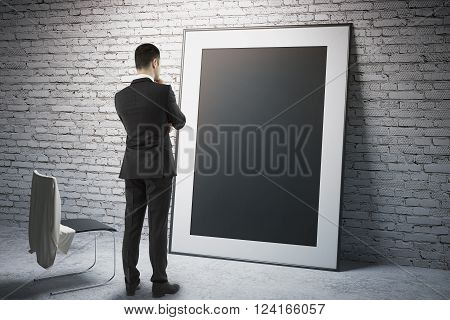 Blank black frame leaning on brick wall with thoughtful businessman staring at it. Mock up 3D Render