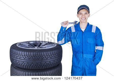 Portrait of a cheerful car mechanic smiling at the camera while holding a wrench near the tires