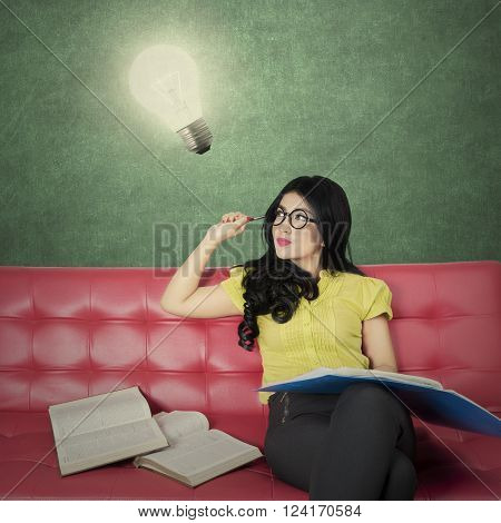 Portrait of a creative female student reading book on the sofa while looking at a bright light bulb