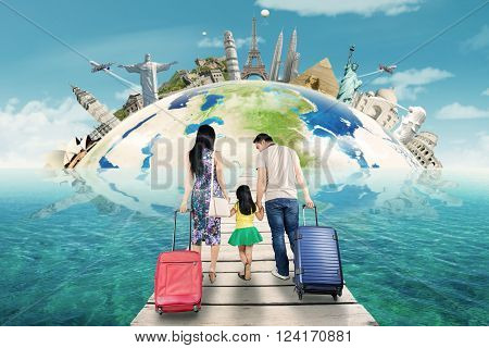 Happy family walking on the jetty while carrying suitcase for traveling to the world monument