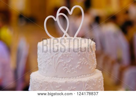 Multi-tiered white wedding cake with two hearts above.