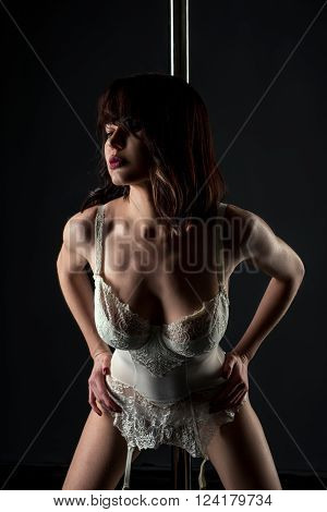 Studio photo of sexy stripper in lace corset with garters