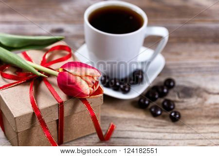 Single tulip resting on gift box with a cup of coffee and dark chocolate in background on rustic wood. Selective focus on front part of flower. ** Note: Shallow depth of field