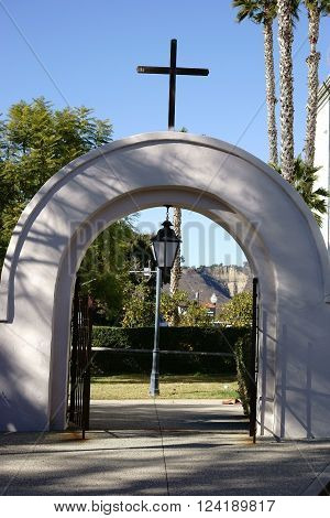 SAN JUAN CAPISTRANO, UNITED STATES - DECEMBER 25: The famous gate of the Mission Basilica San Juan Capistrano with a cross on the round arch on December 25, 2015 in San Juan Capistrano.