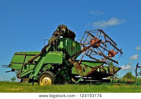 BARNESVILLE, MINNESOTA- June 2, 2014; An old combine with a huge header and wheel is a product of John Deere Co, an American corporation that manufactures agricultural, construction, forestry machinery, diesel engines, and drivetrains.