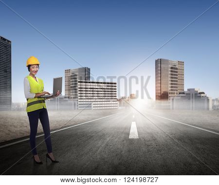 Asian business woman in safety vest standing on the building rooftop while holding laptop
