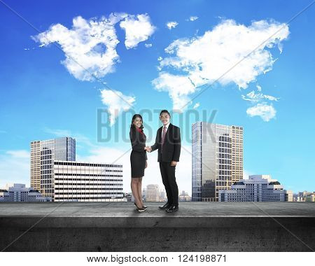 Asian business man and woman shaking hand with world map cloud shape