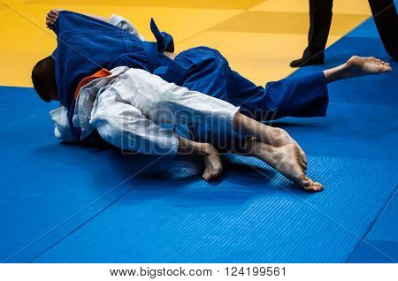 Two judoka in kimono compete on the tatami ** Note: Visible grain at 100%, best at smaller sizes