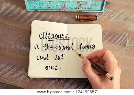 Retro effect and toned image of a woman hand writing on a notebook. Handwritten quote Measure a thousand times and cut once as inspirational concept image