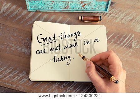 Retro effect and toned image of a woman hand writing on a notebook. Handwritten quote Good things are not done is a hurry as inspirational concept image