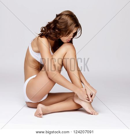 Slim tanned woman's body Isolated over gray background poster