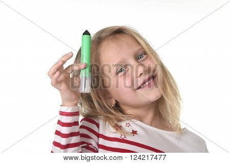 sweet beautiful female child 6 to 8 years old with blonde hair and blue eyes holding drawing - writing marker isolated on white background in education and primary or junior school supplies concept