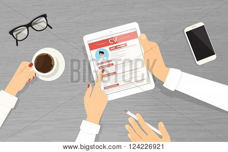 HR managers searching an employee using tablet pc in the office.  Employers are looking at the tablet pc display and reading new employer  cv. Top view with textured table, smartphone, glasses and coffee mug