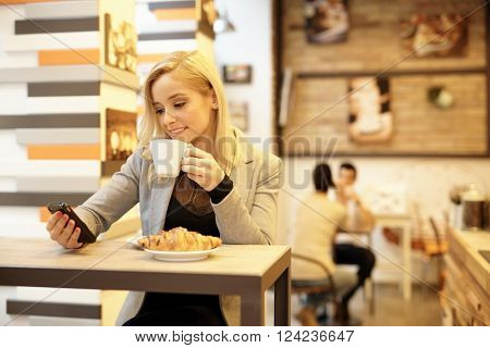 Young blonde woman having breakfast in cafeteria, reading text message on mobilephone.