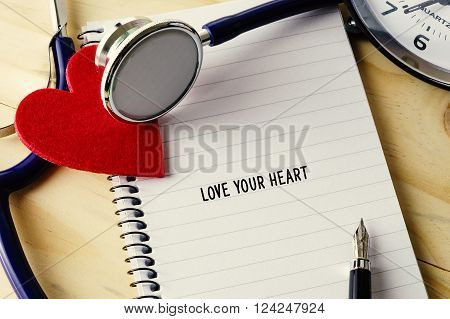 Medical Concept. Stethoscope, Heart Shape, Notepad, Clock And Pen On Wooden Table With Love Your Hea
