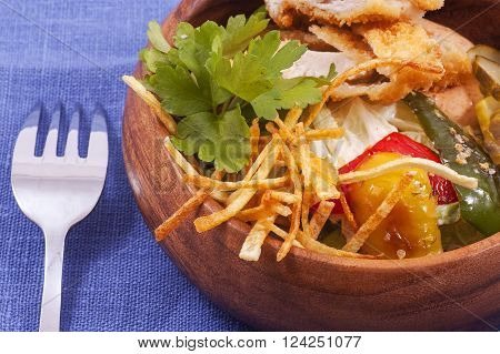 salad with grilled chicken and roasted vegetables on wooden plate close up