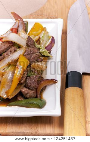 cooked meat with vegetables close-up on a background of a wooden board with knife