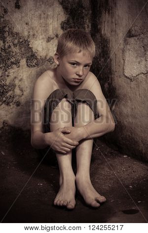 Apprehensive single imprisoned male child wearing shorts sitting on floor with arms around knees in dark, dirty dungeon with stone walls