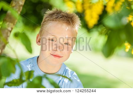 Tilted angle view on cute smiling little blond boy with hazel colored eyes framed by green leaves on tree in shade