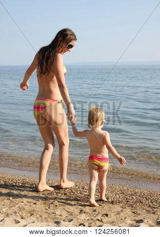 Mother and daughter in same bikinis going into the water