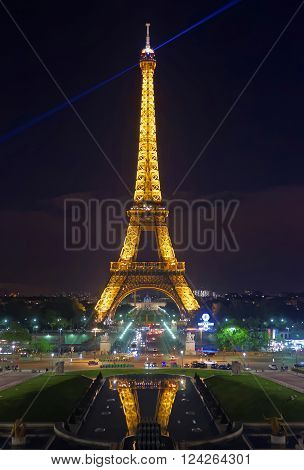 PARIS FRANCE -MAY 2 2012: Illuminated Eiffel Tower on Champ de Mars in Paris France in the evening. Eiffel Tower is an iron lattice tower on the Fields of Mars. It is an icon of France
