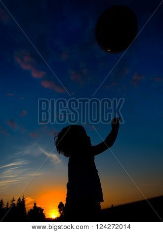 silhouette of a child playing with ball