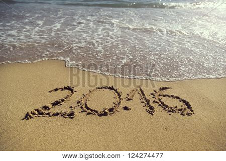 Numbers 2016 handwritten in golden sand on the beach next to the waterline representing new summer season