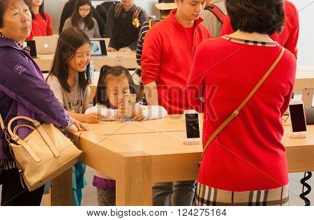HONG KONG, CHINA - FEB 12: Unidentified girls using smartphone inside iStore with many iPhones and gadgets on February 12, 2016. Store sells Macintosh computers software iPod iPad other electronics