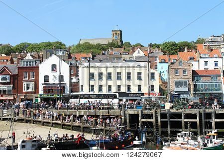 SOUTH BAY HARBOR, SCARBOROUGH, NORTH YORKSHIRE, ENGLAND - 19th of May 2014: Tourists enjoying a day out in the popular seaside resort of Scarborough, North Yorkshire, England