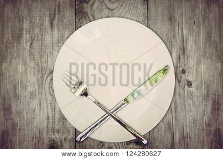 Stop eat concept. Wooden table with empty plate and crossed silver cutlery symbolizing to refuse food. Still life symbolize dieting or unhealthy eating.