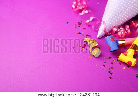 Dotted Birthday hat with serpentine streamer and noise makers on purple background