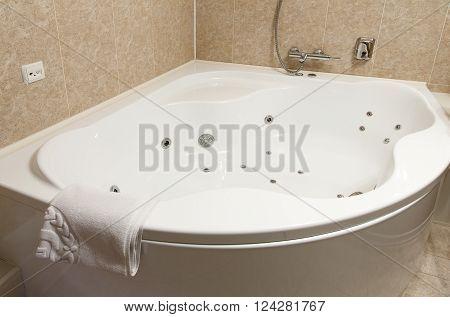 Interior design of a hotel bathroom, jacuzzi, whirpool bath. Hotel restroom interior design. Spa, hydromassage bathtub, jacuzzi. Bathroom interior design. Modern bathroom closeup of bath and towel.