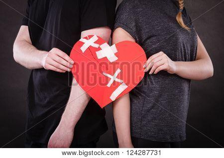 Woman And Man Hands Holds Broken Heart.