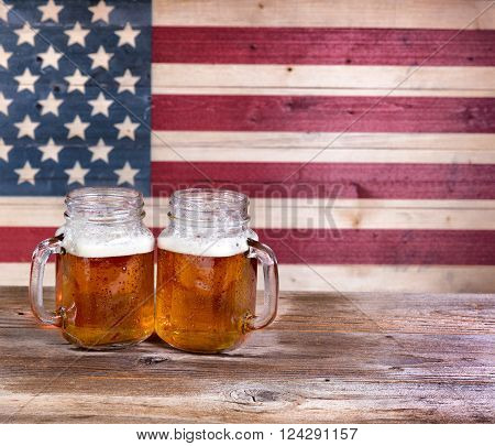 Two pint jars filled with beer with vintage wooden USA flag in background.