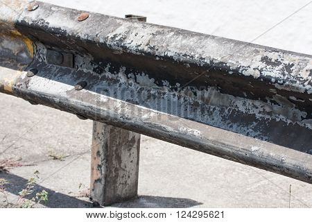 Grungy road guardrail with rusted nails along road