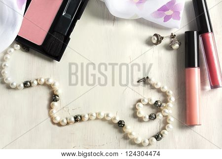 Women's set of fashion accessories on wooden background: pearl neclace earrings lipstick blush and scarf